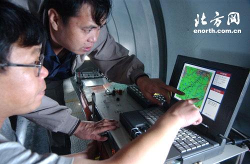 工作人员正在飞机上对增雨情况进行监测