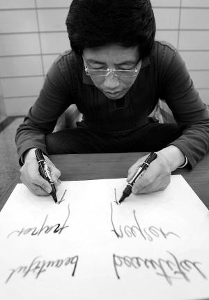天津 男子能双手同时书写对称的中 英文