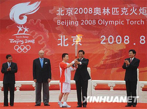 8月6日,第一棒火炬手杨利伟(左三)从中共中央政治局委员、北京市委书记、北京奥组委主席刘淇手中接过火炬。当日,北京奥运圣火在北京市传递。 新华社记者罗晓光摄