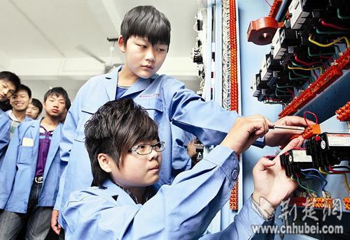 黄士峰 冯亚麟 女孩/冯亚麟(下)在学校做电工电路图接线实验记者黄士峰摄